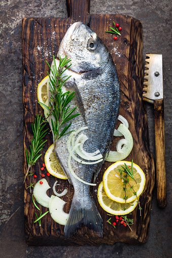 Fresh Fish Dorado With Ingredients For Cooking On Wooden Board Raw Sea Bream Or Dorada Fish On Dark Vintage Metal Background Dietary Food Top View Stock Photo - Download Image Now