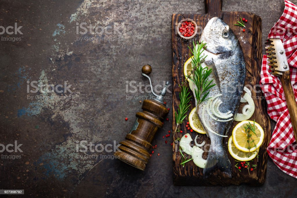 Fresh fish dorado with ingredients for cooking on wooden board. Raw sea bream or dorada fish on dark vintage metal background. Dietary food. Top view - Royalty-free Above Stock Photo