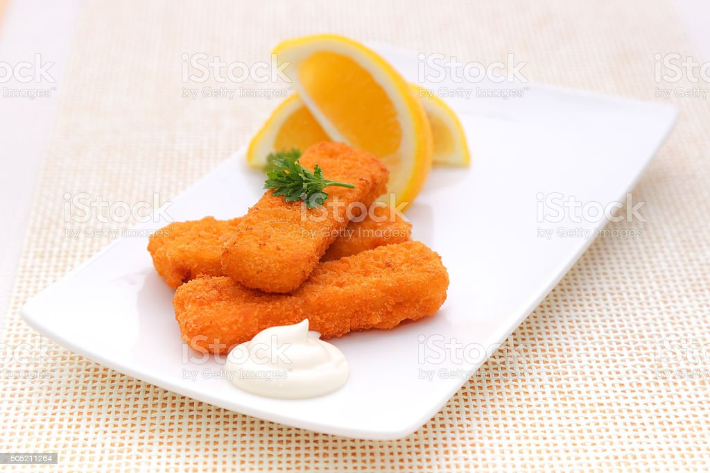 Fresh fish fingers, lemon and white sauce on a plate stock photo