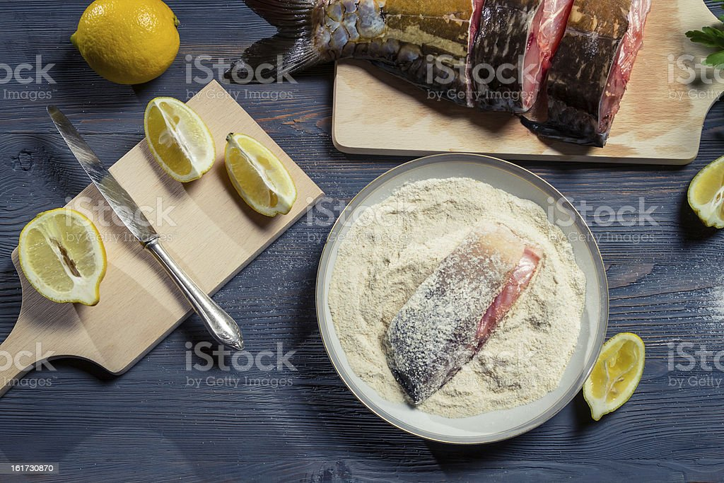 Fresh fish, flour and lemon as ingredients in a dish royalty-free stock photo