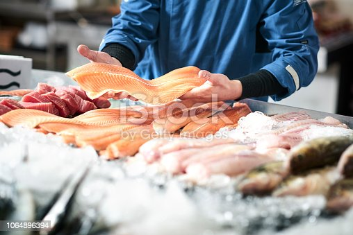 A young male shop assistant in a fishshop saling fresh fish