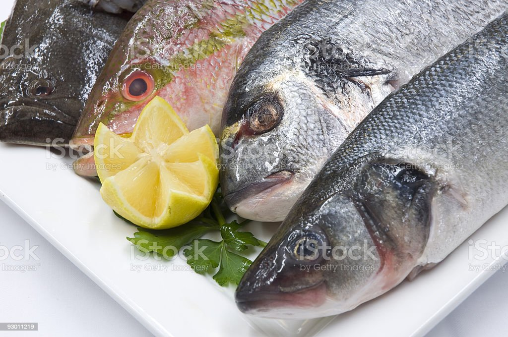 Fresh Fish On A Serving Plate With Lemon Wedge royalty-free stock photo