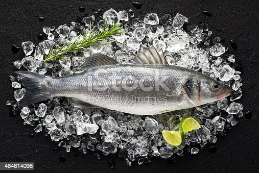 496065234istockphoto Fresh fish on ice on a black stone table 464614098