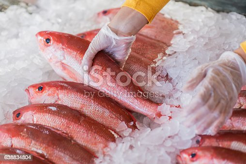 Fresh fish on ice, red snapper, for sale in seafood store. A female worker wearing gloves is taking a whole fish from the display.