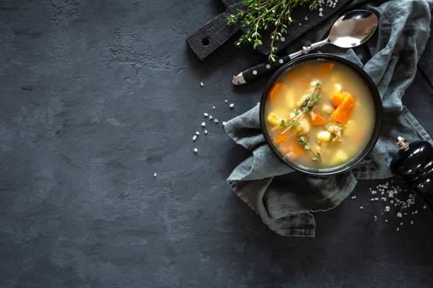 Soupe de poissons frais dans un bol sur fond sombre, vue de dessus - Photo