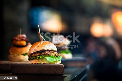 Close up image of a selection of freshly flame grilled burgers in a row on a wooden counter at a London street food market. Each of the burgers has its own label, on which is written the contents of the burger. The burgers are sandwiched between glazed buns, and presented on beds of fresh green lettuce and stuffed with melted cheese and red onion. Horizontal colour image with copy space and beautiful bokeh background.