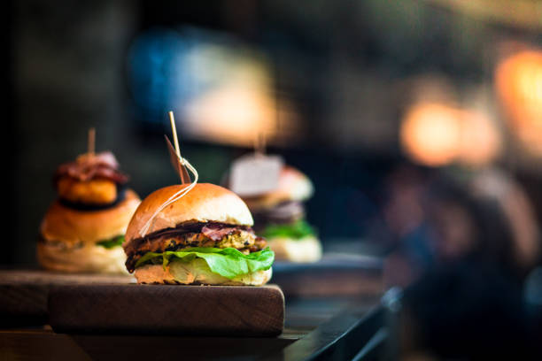 Fresh flame grilled burgers displayed in a row at food market stock photo