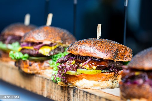 istock Fresh flame grilled burgers displayed in a row at food market 917211354