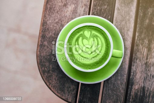 Fresh green matcha with frothy foam, coffee cup top view closeup on gray wooden background. Flat lay style.