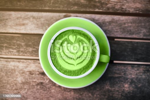 Fresh green matcha with frothy foam, white coffee cup top view closeup on gray wooden background. Flat lay style.