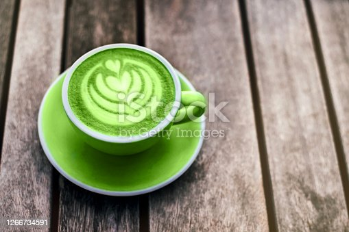 Fresh green matcha with frothy foam, green coffee cup top view closeup on gray wooden background. Flat lay style.