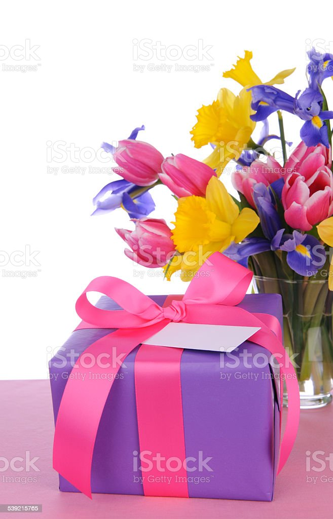Beautiful fresh flowers and a purple gift with a card on a white...