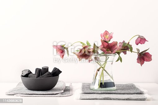 Reusable activated charcoal sticks made from sustainably harvested oak branches purify water for cut garden flowers in mason jars, resting on charcoal infused towels.