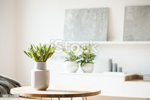 Fresh flowers in white vase placed on small table in bright room interior with paintings, potted plants and candles on shelves in blurred background