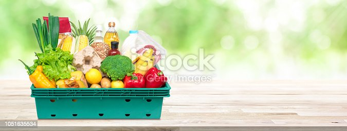 istock Fresh food and groceries in tray box on wood tabletop banner background 1051635534
