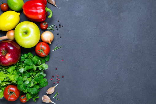 Fresh food background with vegetables, fruits, greens and spices