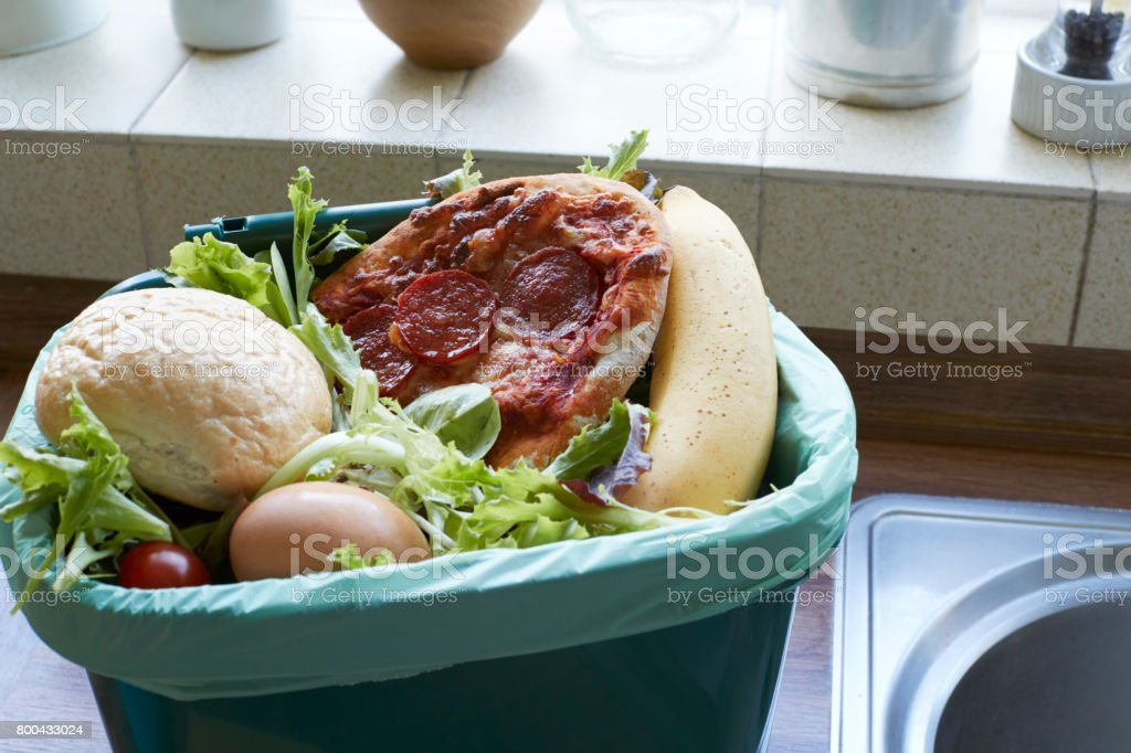 Residuos de alimentos frescos en papelera de reciclaje en casa - foto de stock