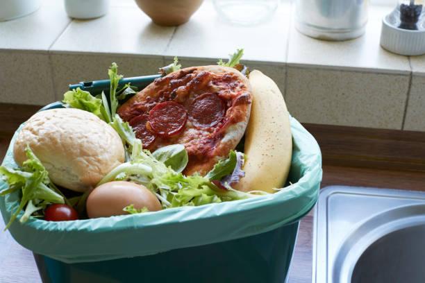 Desperdício de alimentos frescos em reciclagem Bin em casa - foto de acervo