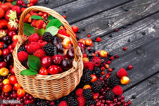 827935944 istock photo Fresh forest berries in basket on rustic wooden background. Copy space 801698234