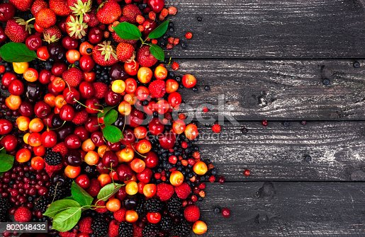 827935944 istock photo Fresh forest berries on rustic wooden background. Copy space, top view 802048432