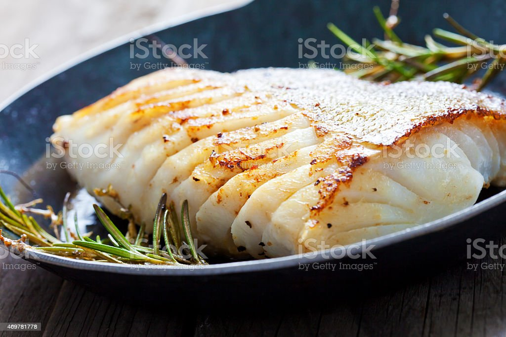 Fresh fried Atlantic cod with rosemary in a frying pan stock photo