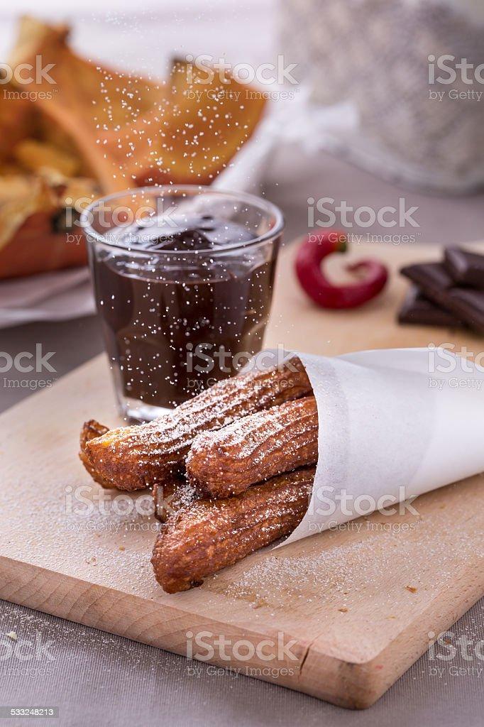 fresh fried pumpkin churros with chocolate on cutting board stock photo