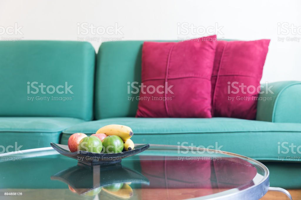 Fresh fruit and green sofa with red backrest pillow in living room stock photo