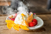 Fresh fruit and vanilla ice cream close up on wood.