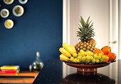 Fresh fruit bowl in modern interior near dark blue wall in the kitchen, beautiful modern design home. pineapple bananas and various fruit retro house closeup