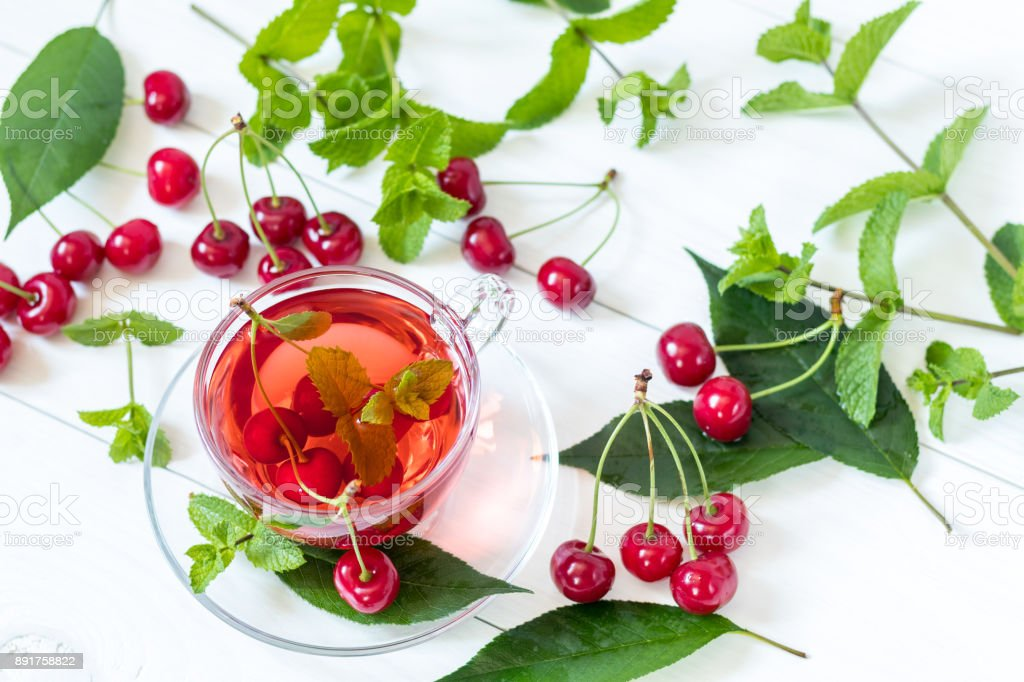 Fresh fruit cherry drink in transparent glass cup surrounded by cherries on the white wooden background. Top view stock photo