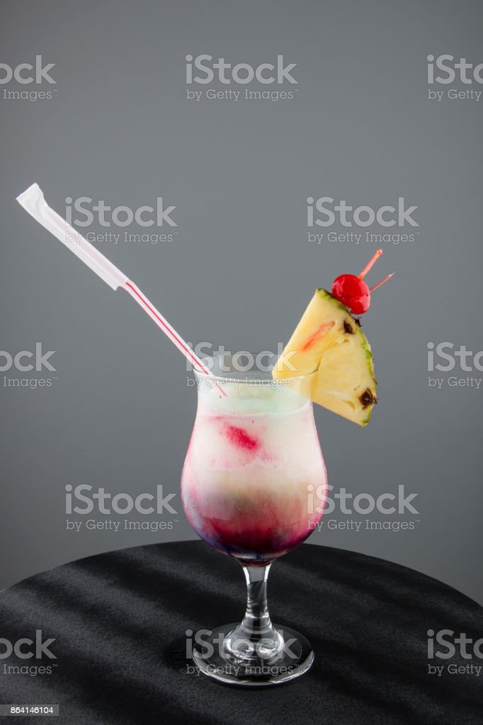 Fresh fruit cocktail with organic pineapple slice and cherry on gray background royalty-free stock photo