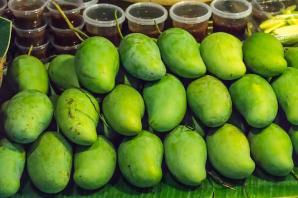 Fresh Fruit Green Mangoes with Sauce Dip on Shelf in Fresh Fruit market Thailand Travel Background Concept stock photo