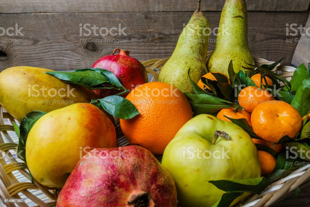 Fresh fruit in a basket on wooden table. stock photo