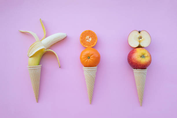 Fresh fruit in ice cream on pink background stock photo