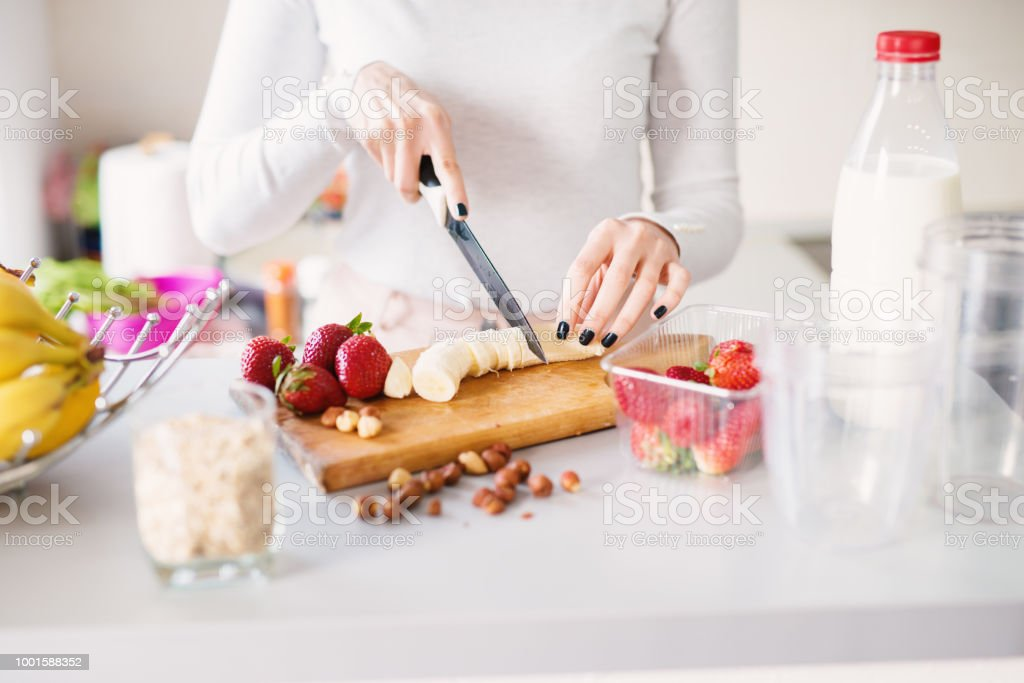 Fresh fruit is being cut into pieces on kitchen counter beside milk and cereals. stock photo