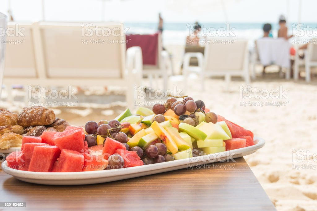 Fresh fruit platter on beach stock photo