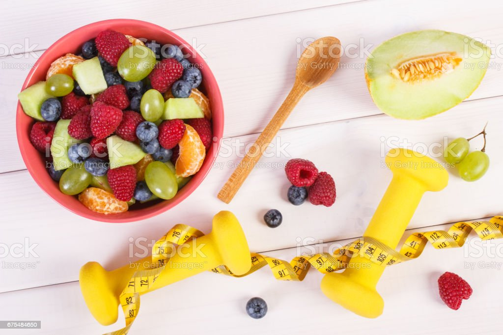 Fresh fruit salad and centimeter with dumbbells, healthy lifestyle and nutrition concept photo libre de droits
