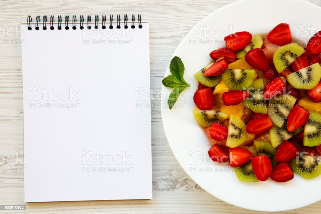 Fresh fruit salad and notebook on white wooden background, top view. From above. - Royalty-free Blank Stock Photo