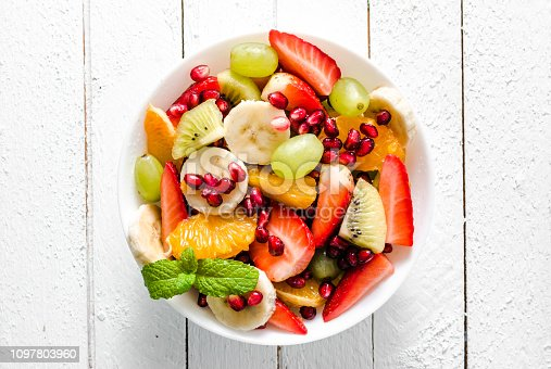 640978994 istock photo Fresh fruit salad in a bowl on white wooden background 1097803960