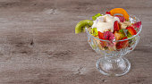 fresh fruit salad in a glass container on a wooden background. richest source of nutrients and vitamins. juicy and fresh berries, the concept of healthy and dietary food.