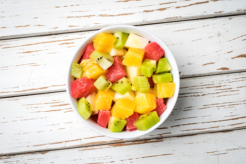 Fresh fruit salad on an old white wooden table