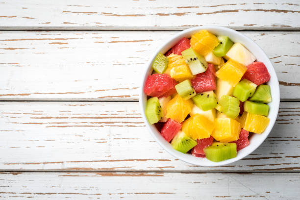 Fresh fruit salad on an old white wooden table Fresh fruit salad on an old white wooden table. Close up fruit salad stock pictures, royalty-free photos & images
