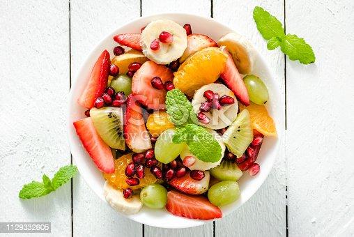 640978994 istock photo Fresh fruit salad on white wooden background 1129332605
