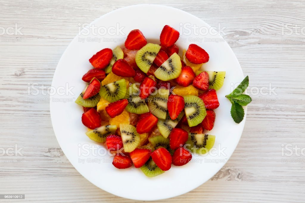 Fresh fruit salad on white wooden background, top view. Flat lay. From above. - Royalty-free Bowl Stock Photo
