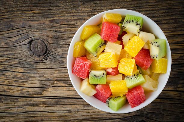 Fresh fruit salad on wooden table stock photo