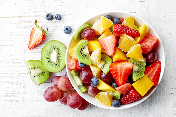Fresh fruit salad Bowl of healthy fresh fruit salad on wooden background. Top view. fruit stock pictures, royalty-free photos & images