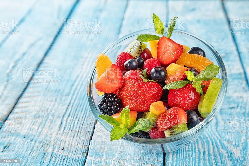 Fresh fruit salad served on wooden table stock photo