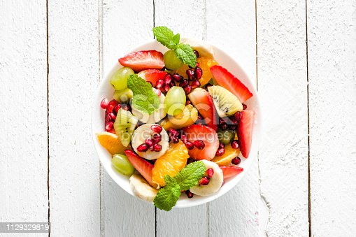 640978994 istock photo Fresh fruit salad, top view in a bowl on wooden background, vegetarian food concept 1129329819