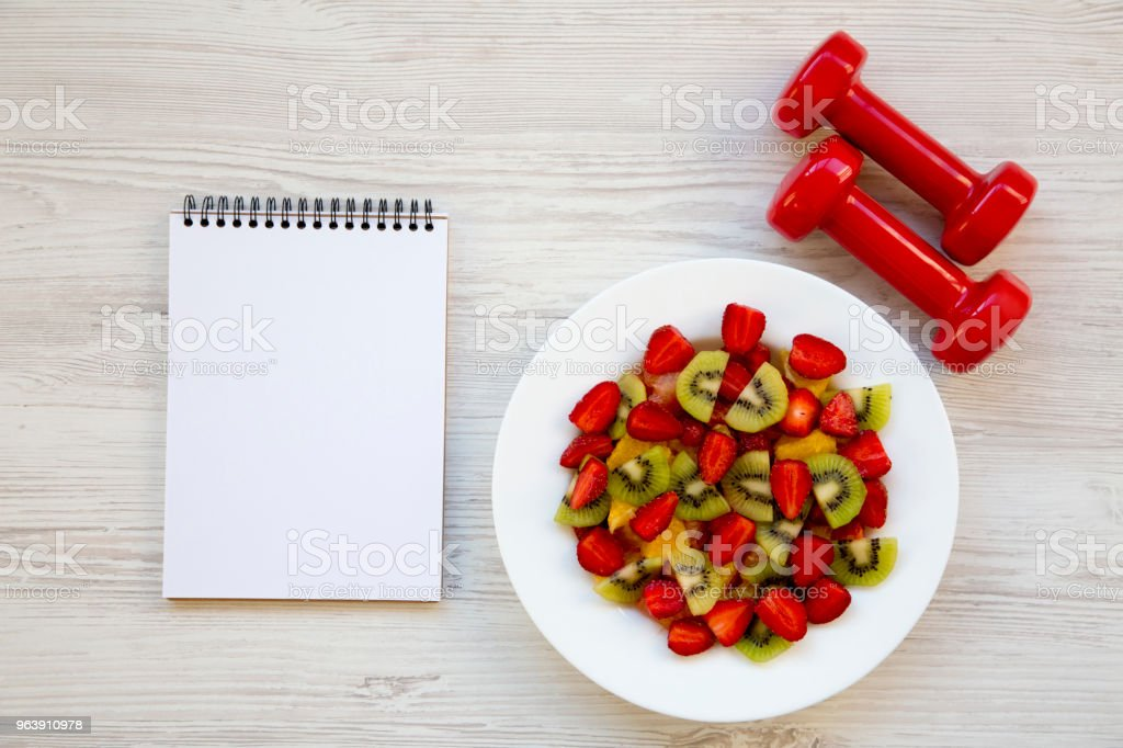 Fresh fruit salad with dumbbells and notebook, top view. Flat lay. Copy space. - Royalty-free Bowl Stock Photo