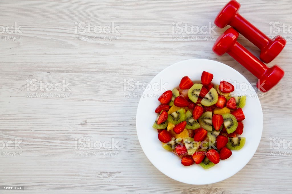 Fresh fruit salad with dumbbells, top view. Flat lay. Copy space. - Royalty-free Bowl Stock Photo